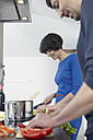 Germany, Cologne, Man and woman cooking together in kitchen - RHYF000122