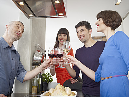 Germany, Cologne, Men and women drinking wine in kitchen - RHYF000146