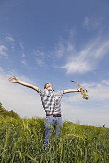 Germany, Hamburg, Teenage boy stretching arms and holding saxophone in nature - MSF002680