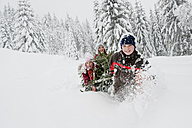 Austria, Salzburg County, Boy and girl pulling christmas tree in snow - HHF004253