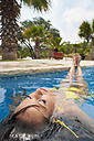 USA, Texas, Young woman relaxing in swimming pool - ABAF000019