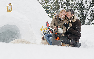 Austria, Salzburg County, Couple sitting near fireplace, smiling - HHF004298