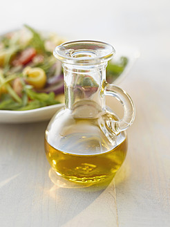 Oil bottle in front of an salad - KSWF000958