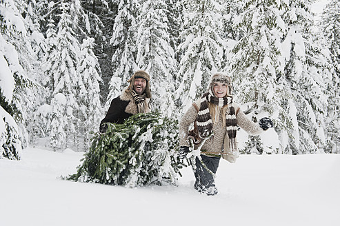 Austria, Salzburg County, Couple pulling christmas tree in winter landscape - HHF004290