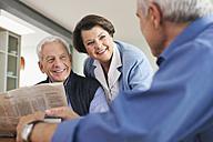 Germany, Leipzig, Senior man reading newspaper, man and woman smiling - WESTF018739