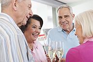 Germany, Leipzig, Senior men and women drinking sparkling wine, smiling - WESTF018811