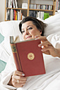 Germany, Leipzig, Senior woman lying on medical bed, reading book - WESTF018820
