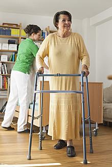 Germany, Leipzig, Senior woman walking with walking frame - WESTF018832