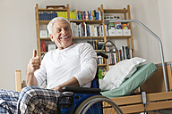 Germany, Leipzig, Senior man sitting on wheelchair, showing thumbs up - WESTF018844