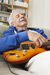 Germany, Leipzig, Senior man plucking guitar - WESTF018877