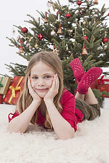 Girl lying on fur carpet, christmas tree and gifts in background - BMYF000331