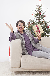 Senior woman sitting on couch with christmas gift, smiling, portrait - BMYF000329