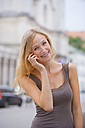 Germany, Bavaria, Munich, Young woman talking on phone in front of Ludwig Maximilian University - TCF002809