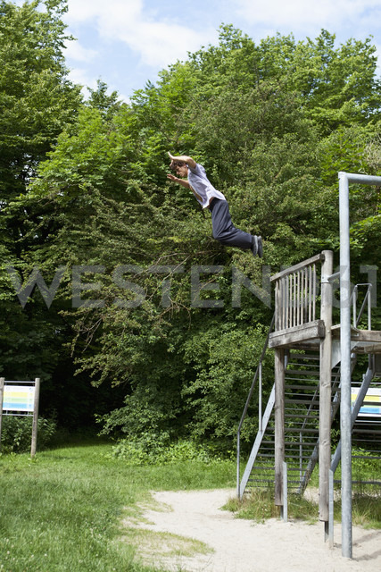 Germany, Bavaria, Young man doing parcour training in park - MAEF004792
