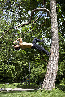 Germany, Bavaria, Young man doing parcour training in park - MAEF004798