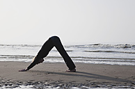 Belgium, Young woman exercising at North Sea - GWF001871