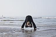 Belgium, Young woman exercising at North Sea - GWF001872