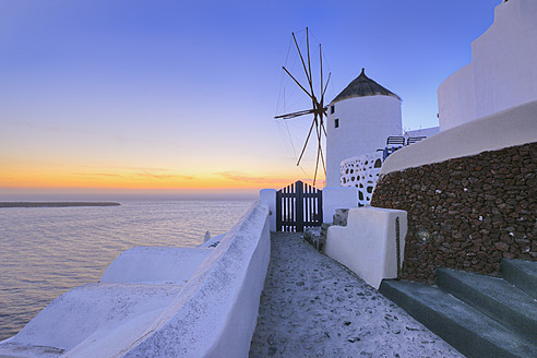 Greece, View of Oia village with traditional Greek windmills in sunset at Santorini - RUEF000957