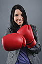 Young woman wearing boxing gloves, portrait, close up - RDF001020
