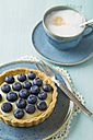 Blueberry tart with vanilla pudding and cappuccino on table - ECF000019