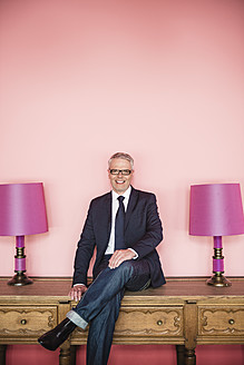 Germany, Stuttgart, Businessman sitting on sideboard with lamps, smiling, portrait - MFP000125
