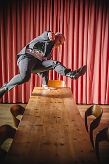 Germany, Stuttgart, Businessman jumping over table in apartment - MFP000137