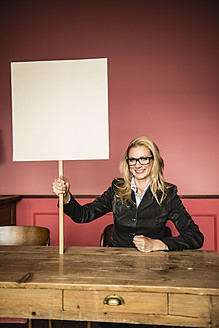 Germany, Stuttgart, Businesswoman holding blank sign, smiling, portrait - MFP000167