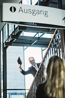 Germany, Stuttgart, Businessman showing diary to woman on stairs of office building - MFPF000200