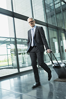 Germany, Stuttgart, Businessman pulling luggage in office building - MFPF000209