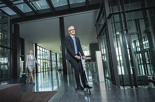 Germany, Stuttgart, Businesswoman with wheeled luggage, man riding scooter at office building - MFPF000212