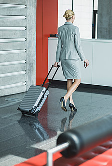 Germany, Stuttgart, Businesswoman walking with wheeled luggage - MFPF000224