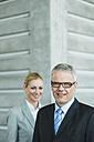 Germany, Stuttgart, Business people in office lobby, smiling, portrait - MFPF000227
