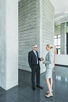 Germany, Stuttgart, Business people having discussion at office lobby - MFPF000230