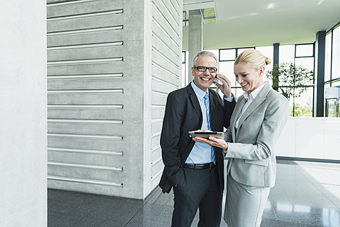 Germany, Stuttgart, Businesswoman with digital tablet while man talking on phone - MFPF000233