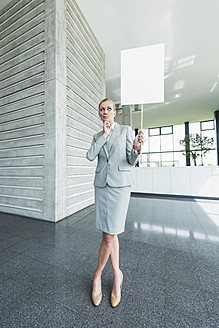 Germany, Stuttgart, Businesswoman standing with blank signs in office lobby - MFPF000236