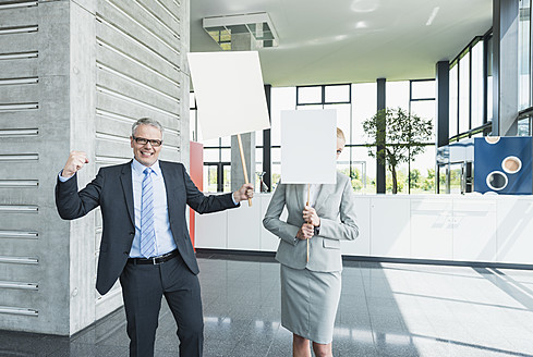 Germany, Stuttgart, Business people holding blank signs in office lobby, smiling - MFPF000242