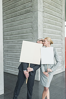 Germany, Stuttgart, Business people holding blank signs in office lobby, kissing - MFPF000245