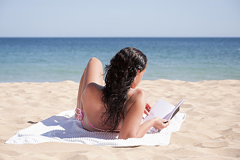 Portugal, Lagos, Mid adult woman reading book on beach - UMF000352
