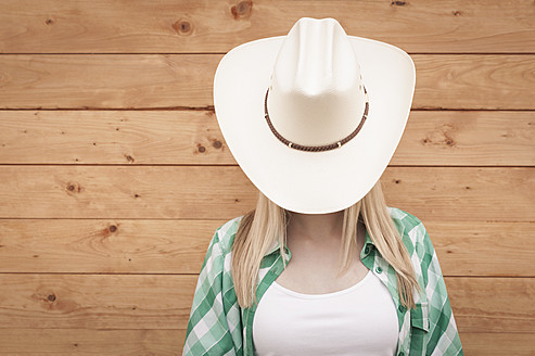 Germany, Teenage girl covering face with cowboy hat - KJF000164