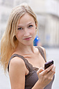 Germany, Bavaria, Munich, Young woman standing with smart phone in front of Ludwig Maximilian University - TCF002819