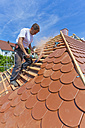 Germany, Baden-Wuerttemberg, Stuttgart, Mid adult man cutting roof tile - WDF001276