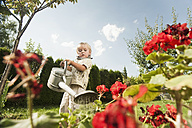 Germany, Bavaria, Boy watering garden flowers - RNF000976