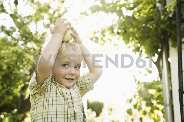 Germany, Bavaria, Boy playing with apple on top of head - RNF000987
