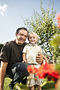 Germany, Bavaria, Father and son smiling, portrait - RNF000989