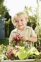 Germany, Bavaria, Boy holding bundle of radish, smiling - RNF000994