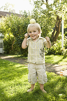 Germany, Bavaria, Boy playing with apple on top of head - RNF000996