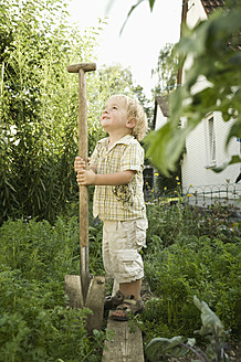 Germany, Bavaria, Boy holding shovel in garden - RNF001000