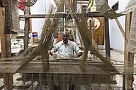 India, Uttar Pradesh, Banaras, Man weaving loom - FO004207