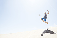 France, Teenage boy jumping on sand dune after football - MSF002752