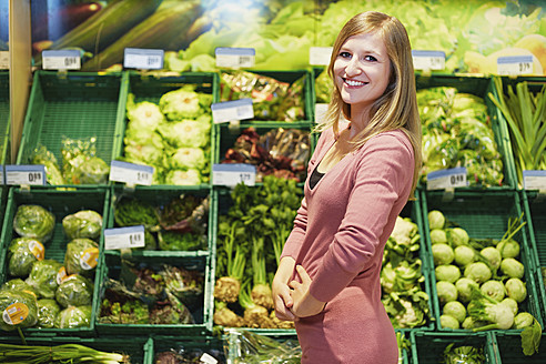 Germany, Cologne, Young woman in supermarket, smiling, portrait - RKNF000003